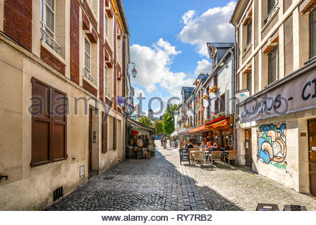 Tourists having lunch at a sidewalk cafe on a picturesque back street in the Normandy village of Honfleur, France. - Stock Image