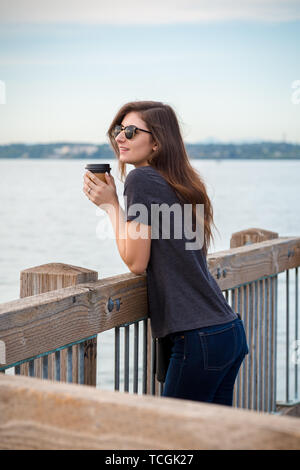 A pretty young brunette woman wearing sunglasses with a coffee on an oceanside boardwalk enjoying the ocean view. - Stock Image