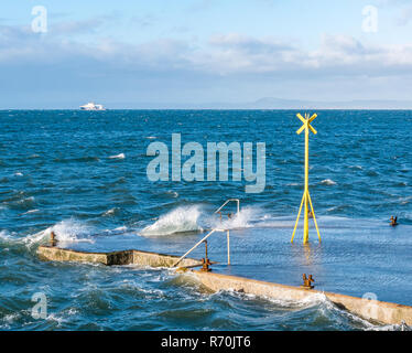 North Berwick, East Lothian, Scotland, United Kingdom. 7th December 2018. UK Weather: A bright sunny but very windy day in the seaside town with gusts of wind of up to 50-60mph forecast for today. Waves splash on the pier - Stock Image