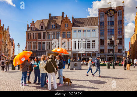 25 September 2018: Bruges, Belgium - Tour group under orange umbrellas in the centre of the city, Markt Square, on a sunny, autumn day with glorious b - Stock Image