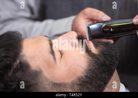 Barber shaving the beard of a handsome bearded man with an electric razor at the barber shop . - Stock Image