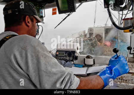 At the helm in the wheel house navigating the vessel. - Stock Image