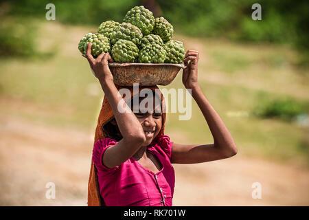 Girl selling vegetables on roadside - Stock Image