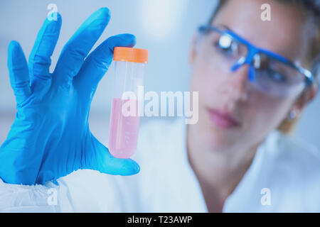 Young female scientist holding liquid sample. - Stock Image