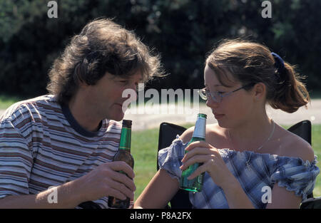 father/male adult drinking bottle of beer with teenage girl/daughter - Stock Image
