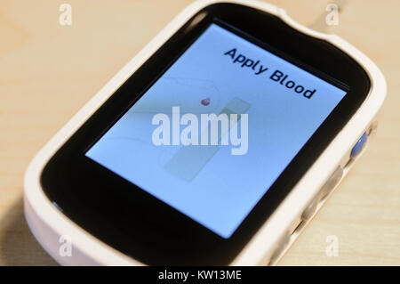Blood glucose monitor asking the user to apply blood to the test strip - Stock Image