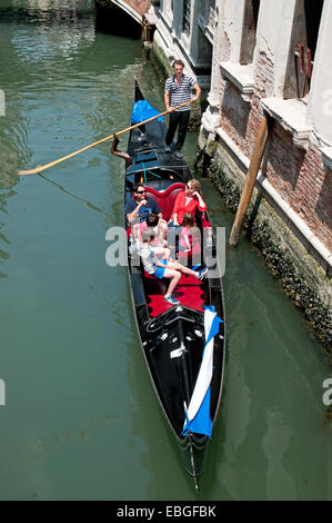 Family enjoying a gondola ride on canal Rio de la Canonica Venice Italy seen from bridge above - Stock Image