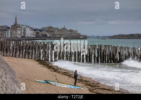 View of sea and groynes along promenade at seafront with Intra Muros in the background, Saint Malo, Brittany, France - Stock Image