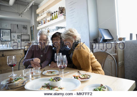 Active senior women friends with camera phone enjoying appetizers and red wine in cafe - Stock Image