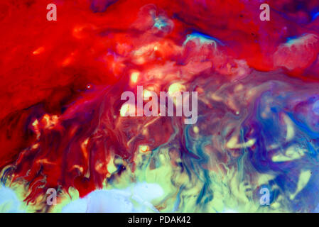 Abstract liquid milk flowing pattern like nebulae in the universe with different colours of white, blue, red and pink - Stock Image