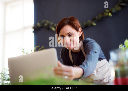 A young creative woman arranging flowers in a flower shop, using laptop. A startup of florist business. - Stock Image