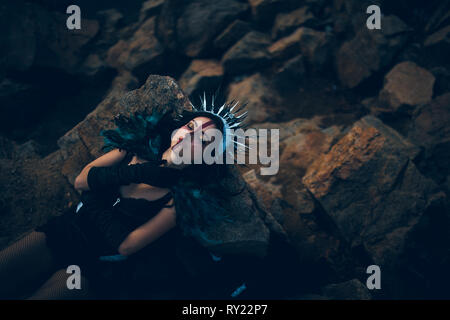 A young woman in the image of a fairy and a sorceress lying on rock in a black dress and a crown. - Stock Image