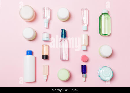 Group of plastic bodycare bottle Flat lay composition with cosmetic products on pink background empty space for you design. Set of White Cosmetic cont - Stock Image