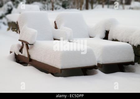 forgotten sun beds in snow - Stock Image