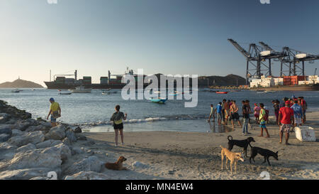 Locals on the beach with a container ship leaving port beyond, Santa Marta, Magdalena, Colombia - Stock Image