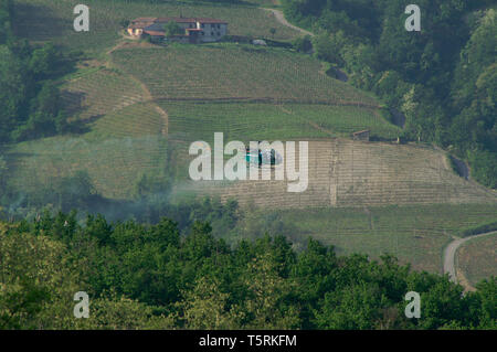 Photo Needs. Archival aerial spraying by helicopter over vineyards, Italy. - Stock Image