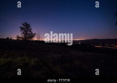 Scenic view of silhouette landscape at dusk - Stock Image