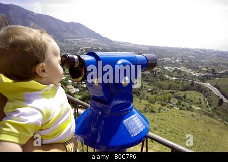 Toddler looking through a telescope, Mijas Pueblo, Costa del Sol,  Andalucia, Spain - Stock Image