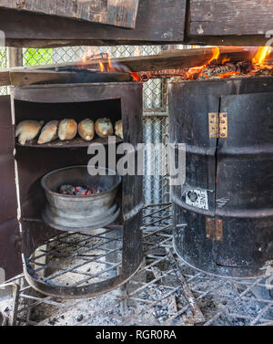 Rustic roadside bakery made from oil drums and car wheels. Saint Lucia, Caribbean. - Stock Image