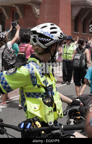 Female Western Australian police bicycle officer keeping an eye on proceedings at a public event. - Stock Image