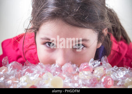 Little child girl look to the camera behind lots of wrapped soft jelly gummies. Closeup - Stock Image