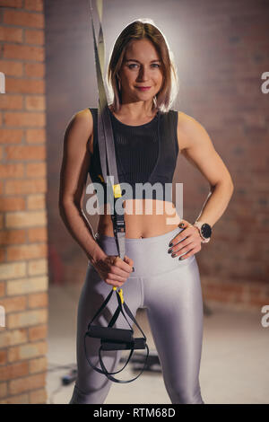 Sports Girl looking at camera while engaging in TRX functional workout in loft style gym. - Stock Image