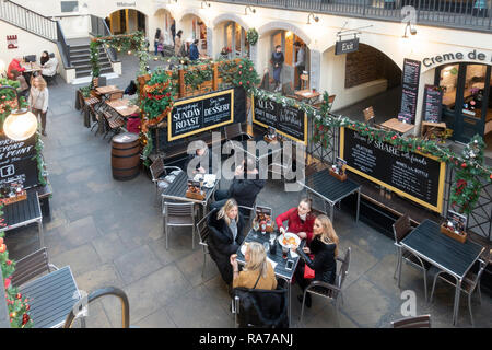 Elevated view of people eating and browsing in the piazza of the Covent Garden Market Building in central London, England, UK. - Stock Image