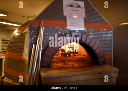 Fire in dome ceramic wood burning pizza oven in the kitchen of Amsterdam Brewhouse restaurant Toronto - Stock Image