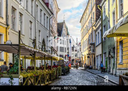 Tourists sightsee and enjoy sidewalk cafes in the historic Old Town of the medieval city of Tallinn, Estonia. - Stock Image