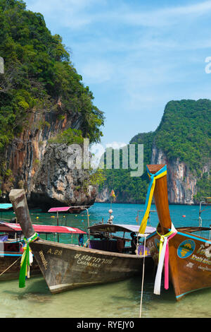 Traditional Thai longtail boats on the beach in Koh Lao La Ding island - Stock Image