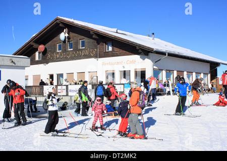 Skiers in front of restaurant Schwarzseespitze, Rittner Horn / Corno del Renon, Dolomite Alps - Stock Image