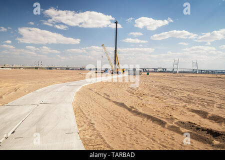 Site ready for building construction. Panoramic landscape with sand, drilling machine and distant city horizon - Stock Image