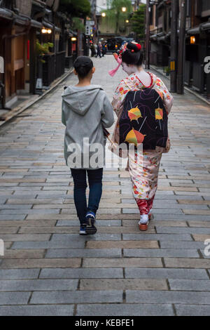 A geiko and her chaperone walking down a street in Gion, Kyoto - Stock Image
