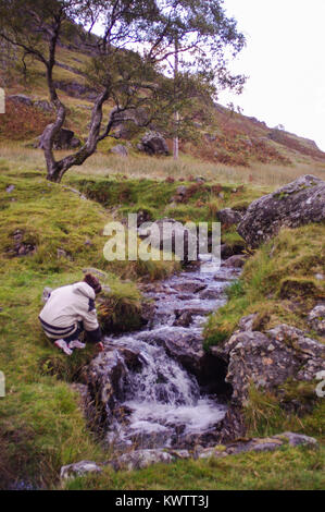 Woman plays at edge of mountain stream - Stock Image
