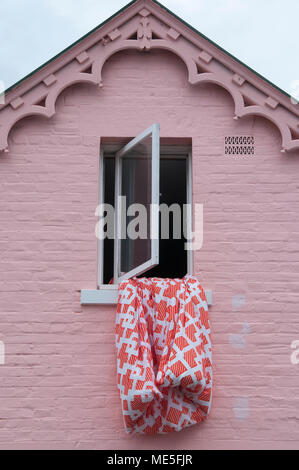 Bedding hung out to dry from the attic window of a Victorian Gothic style house in Battery Point, Hobart, Tasmania, Australia - Stock Image