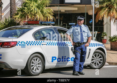 New South Wales police man stood by his police car in Sydney,Australia - Stock Image