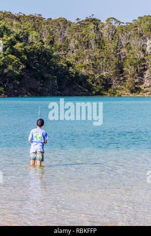 Boy fishing, beach by Pambula river estuary, New South Wales, Australia - Stock Image
