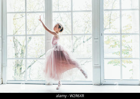 Young classical ballet dancer girl in dance class. Beautiful graceful ballerina practice ballet positions in pink tutu skirt near large window in whit - Stock Image