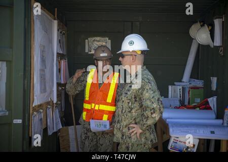 ROTA, Spain (March 15, 2019) Utilitiesman 1st Class Josue Gonzalez, assigned to Naval Mobile Construction Battalion (NMCB) 133, discusses the progress of the Tow Way Street lighting project site with Rear Adm. John Korka, commander of Naval Facilities Engineering Command, during his visit to Camp Mitchell onboard Naval Station Rota, Spain. NMCB-133 is forward deployed to execute construction, humanitarian and foreign assistance, and theater security cooperation in the U.S. 6th Fleet area of operations. - Stock Image