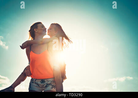 Mother and daughter playing together outdoor - Happy family piggyback at sunset - Parenthood, childhood, love and happiness concept - Stock Image