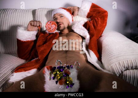 Handsome naked santa with open jacket sixpack abs with stocking stuffed with sweets and candy canes licking lollipop - Stock Image