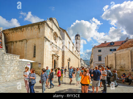 Crowds of tourists walk the main street or stradun next to St Saviour Church in the ancient walled city of Dubrovnik, Croatia. - Stock Image