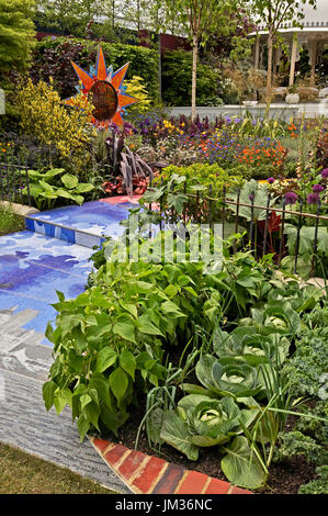 A contemporary garden with colourful borders of flowers and vegetables - Stock Image