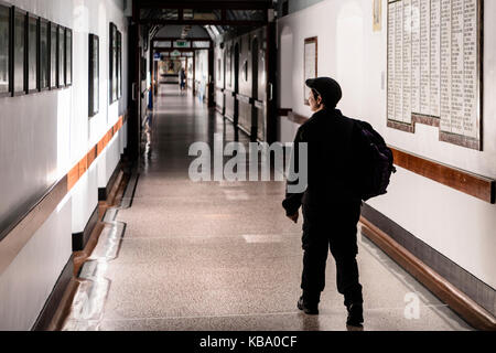 A man wearing a flat cap walks along the Victorian corridor in the Royal Victoria Hospital, Belfast. - Stock Image