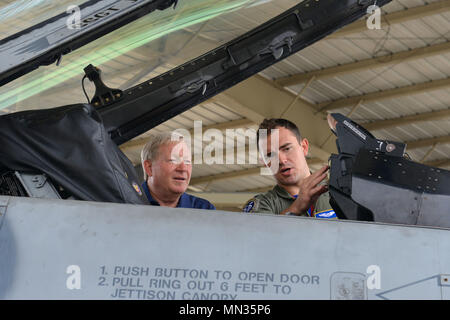 U.S. Air Force Capt. Chris Jeffers, 55th Fighter Squadron (FS) F-16CM Fighting Falcon pilot, shows Daniel Clark, 55th FS veteran, the inside of an F-16 cockpit at Shaw Air Force Base, S.C., Aug. 25, 2017. During the alumni tour, 55th veterans who flew and maintained various airframes, from the P-51 Mustang to the F-111 Aardvark, were briefed on F-16 capabilities. (U.S. Air Force photo by Airman 1st Class Destinee Sweeney) - Stock Image