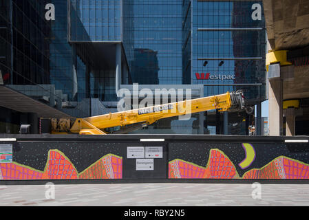 A yellow construction crane sits folded down behind a colourful hoarding in front of the Westpac Bank building at Barangaroo South in Sydney city. - Stock Image
