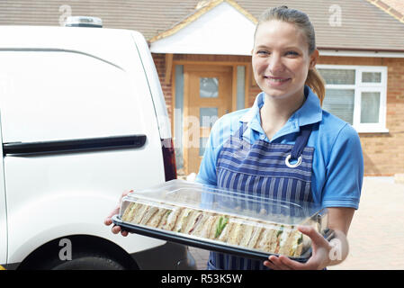 Female Caterer Delivering Tray Of Sandwiches To House - Stock Image