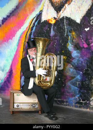 Elderly man playing a tuba shooting fire from the top - Stock Image