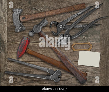 vintage blacksmith or metalwork tools over wooden bench, blank plate and business card for your text - Stock Image