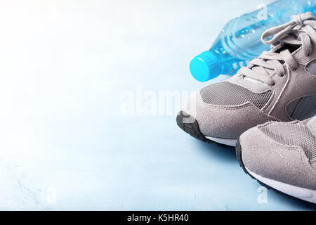 Gray sneakers and a bottle of water on a blue background. view from above - Stock Image